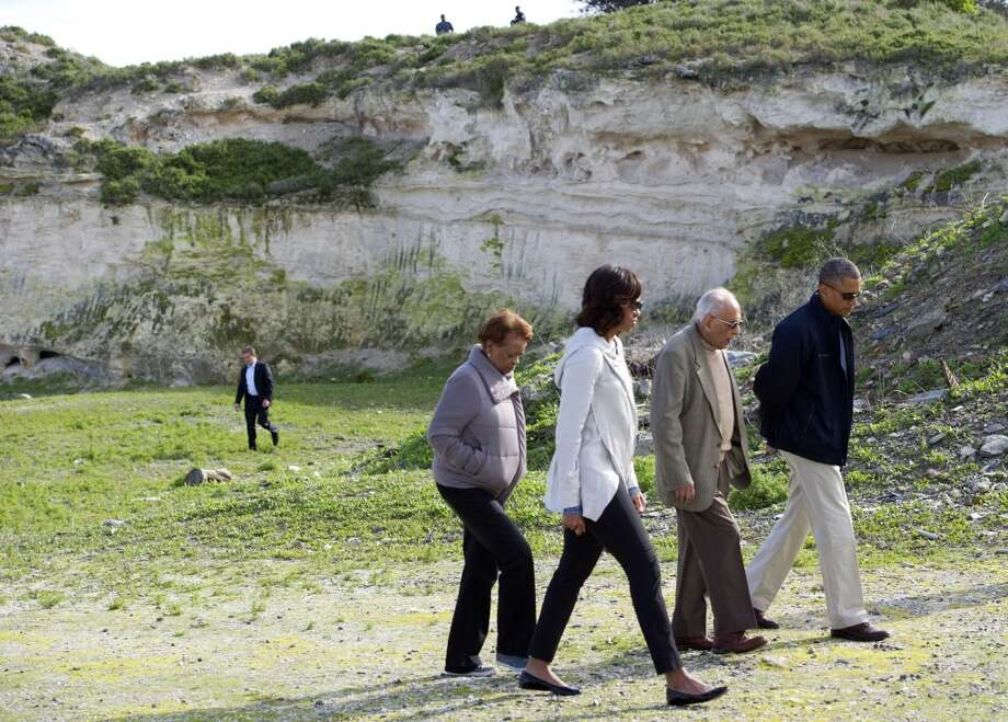"US President Barack Obama (R), First Lady Michelle Obama (2L) listen to former prisoner Ahmed Kathrada (C) with Michelle Obama's mother Marian Robinson (L) as they tour the limestone quarry where prisoners worked on Robben Island off the coast of Cape Town, South Africa on June 30, 2013. President Barack Obama was ""deeply humbled"" by a visit to the cell where Nelson Mandela spent years as a prisoner, in a solemn homage Sunday to the critically ill hero he was unable to see in Pretoria.  AFP PHOTO / Saul LOEBSAUL LOEB/AFP/Getty Images"