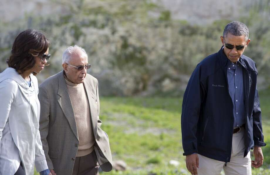 "US President Barack Obama (R) and First Lady Michelle Obama (L) listen to former prisoner Ahmed Kathrada as they tour the limestone quarry where prisoners worked on Robben Island off the coast of Cape Town, South Africa on June 30, 2013. President Barack Obama was ""deeply humbled"" by a visit to the cell where Nelson Mandela spent years as a prisoner, in a solemn homage Sunday to the critically ill hero he was unable to see in Pretoria. AFP PHOTO / Saul LOEBSAUL LOEB/AFP/Getty Images"