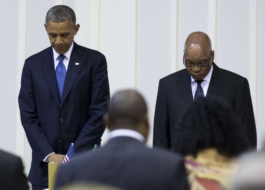 TOPSHOTS South African President Jacob Zuma (R) and US President Barack Obama bow their heads during a moment of prayer for former South African President Nelson Mandela during an official dinner at the Presidential Guest House in Pretoria, South Africa, on June 29, 2013. AFP PHOTO / Saul LOEBSAUL LOEB/AFP/Getty Images