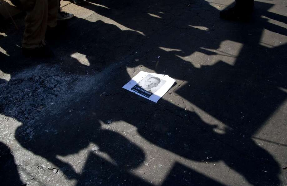 TOPSHOTS A poster of US president Barack Obama is seen between the shadows of protestors demonstrating against the US president's visit to South Africa outside the university in Soweto on June 29, 2013. Police fired stun grenades today at hundreds of protesters rallying against President Barack Obama's visit to South Africa.    TOPSHOTS/AFP PHOTO / ODD ANDERSENODD ANDERSEN/AFP/Getty Images