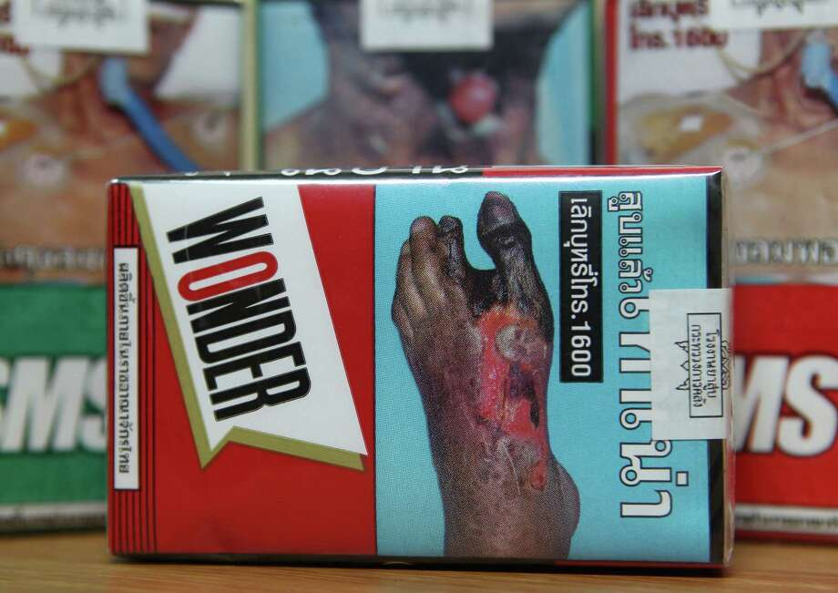 The warning signs are printed on the cigarette packets on sale in Bangkok, Thailand Wednesday, June 26, 2013. Tobacco giant Philip Morris and more than 1,400 Thai retailers will sue Thailand's health ministry over a rule that would nearly cover cigarette packets with smoking warnings, a tobacco trade representative said Wednesday. The regulation scheduled to take effect Oct. 2 requires that 85 percent of space on the packets' front and back be dedicated to warning messages and images, some containing graphic pictures of lung cancer patients. Photo: AP