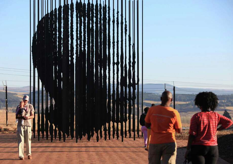 Visitors observe a sculpture depicting former president Nelson Mandela, by artist Marco Cianfanelli, near Howick, South Africa, where Mandela was arrested in 1962 and subsequently jailed for 27 years, Saturday, June 29, 2013. Mandela remains in critical condition in a Pretoria. hospital just weeks before his 95th birthday. Photo: AP