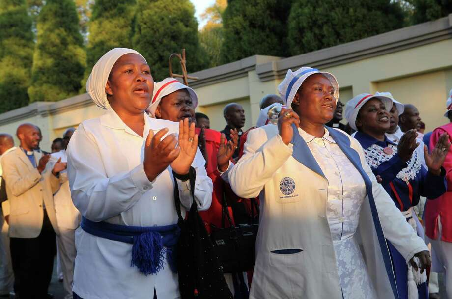 Members of the  First John Apostolic Church sing and  pray for  Nelson Mandelas  recovery outside his residence in Johanesburg,  South Africa,Sunday, June, 30, 2013.Mandela  whose condition  has improved according to the Presidency,remains in a  critical condition in a hospital in  Pretoria. Photo: AP