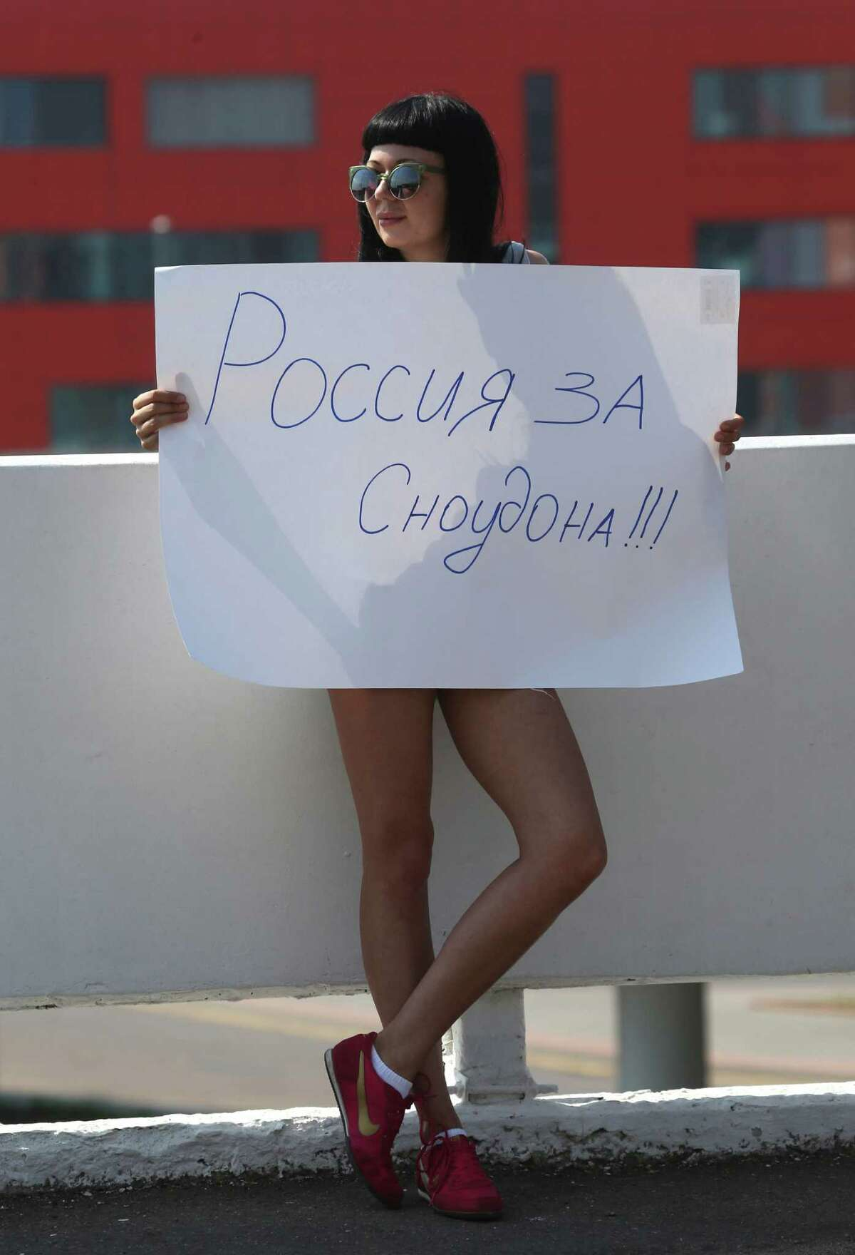 A Snowden supporter holds a poster outside Sheremetyevo, airport in Moscow Friday, June 28, 2013. Russian and foreign journalists continued to monitor the Sheremetyevo international airport, where National Security Agency leaker Edward Snowden is believed to remain at the transit zone. The poster reads: