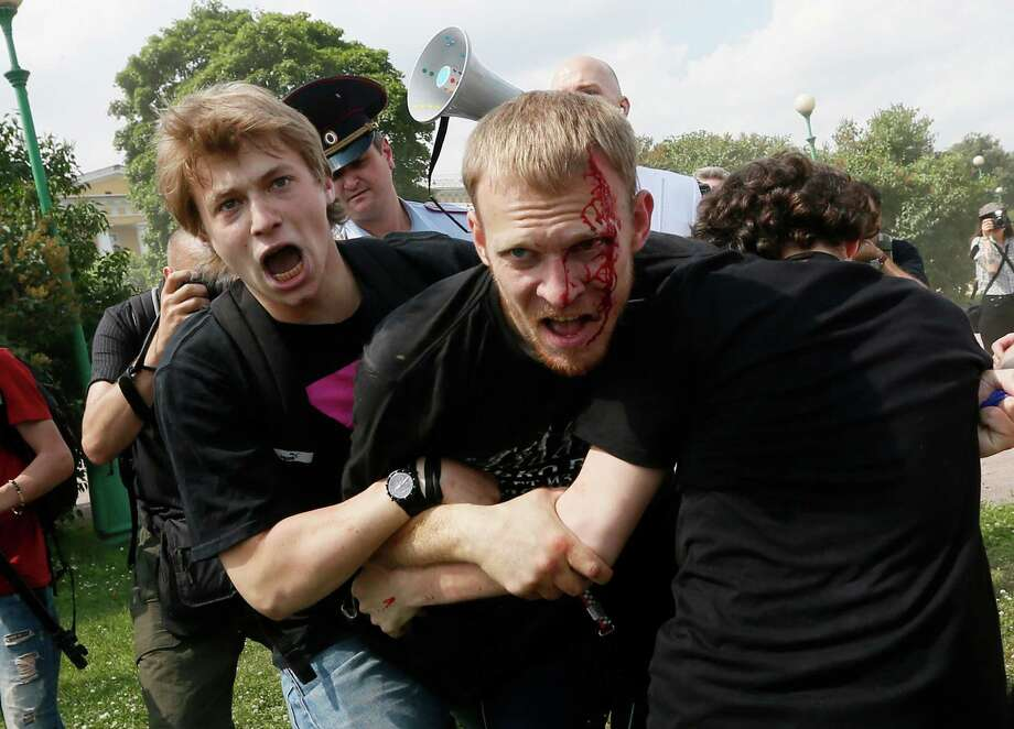 An anti-gay protester, center, fights with gay rights activists during an authorized gay rights rally in St.Petersburg, Russia, Saturday, June 29, 2013.  Police detained several gay activists, who were outnumbered by the protesters. Dozens of gay activists had to be protected by police as they gathered for the parade, which proceeded with official approval despite recently passed legislation targeting gays. Photo: AP