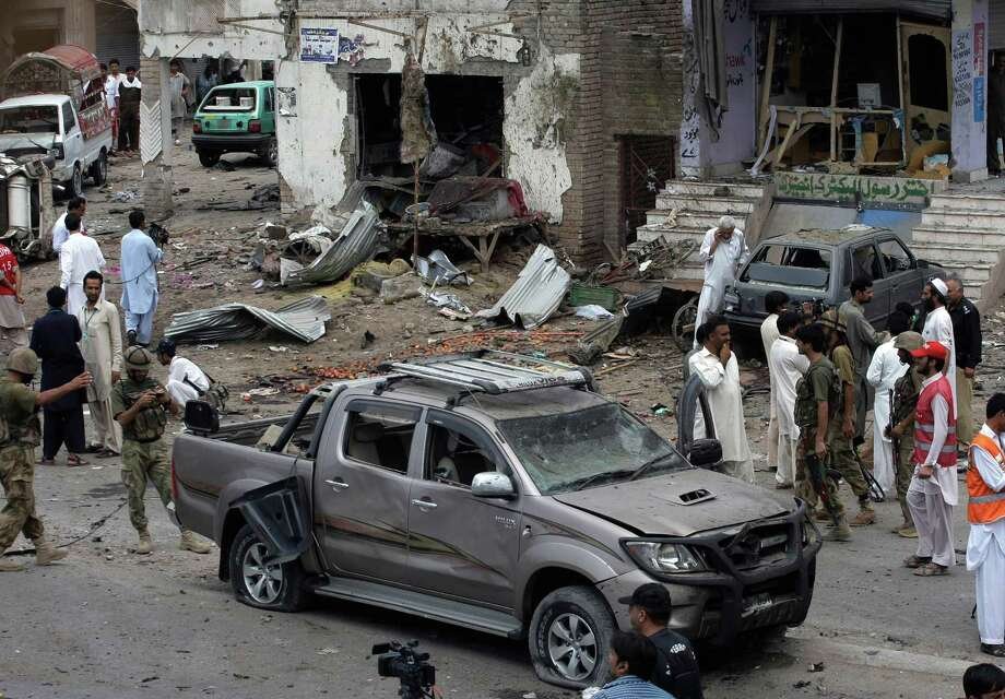 Pakistani security officials and rescue workers examine the site of car bombing on the outskirts of Peshawar, Pakistan, Sunday, June 2013. A car bomb exploded as a convoy of paramilitary troops passed through the outskirts of the northwest Pakistani city of Peshawar, killing more than a dozen people and wounding scores of others, police said. Photo: AP