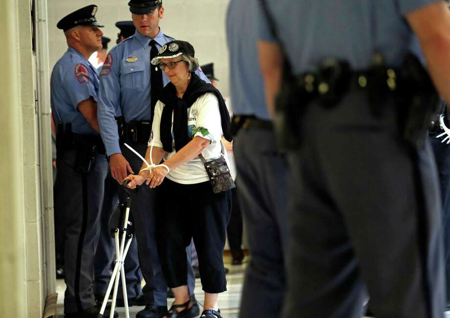 "A woman is arrested during an act of civil disobedience outside the House and Senate chambers during ""Moral Monday"" protests at the General Assembly in Raleigh, N.C., Monday, June 24, 2013. Protesters showing up in growing numbers are angry about the rightward tilt of the state since Republicans gained control of the state legislature and the governor's mansion, the first time they've held both branches of government at the same time since 1870. Photo: AP"