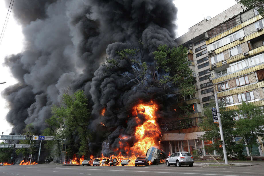 A multi-story building is engulfed by flames after a road accident in downtown Almaty, Kazakhstan, on Thursday, June 27, 2013.  According to witnesses, the fire was a result of a petrol tank lorry that  exploded near Rixos hotel at the crossing killing one person and destroying 20 apartments. Photo: AP