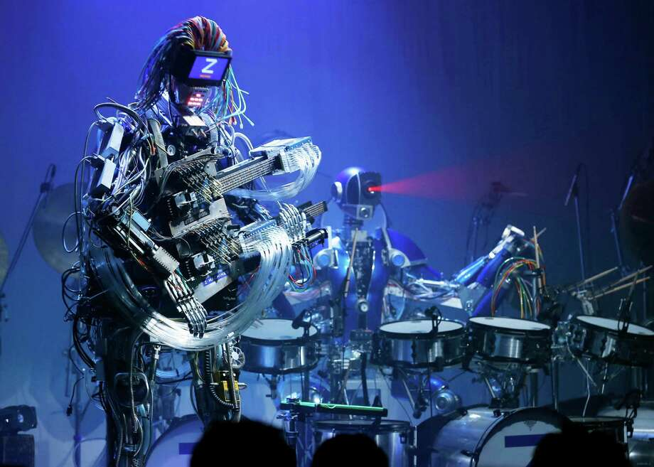 Robot music band Z-Machines members, guitarist robot Mach, left, and drummer robot Ashura, perform at their debut live event in Tokyo Monday, June 24, 2013. Supervised by Japanese artists and creators, Z-Machines has been developed to realize the cutting edge party scene by featuring the guitarist robot with 78 fingers and 12 picks, the drummer robot with 21 sticks and a keyboard player robot that can flash multi-layered beams from its eyes, enabling transcendental music performance. Photo: AP