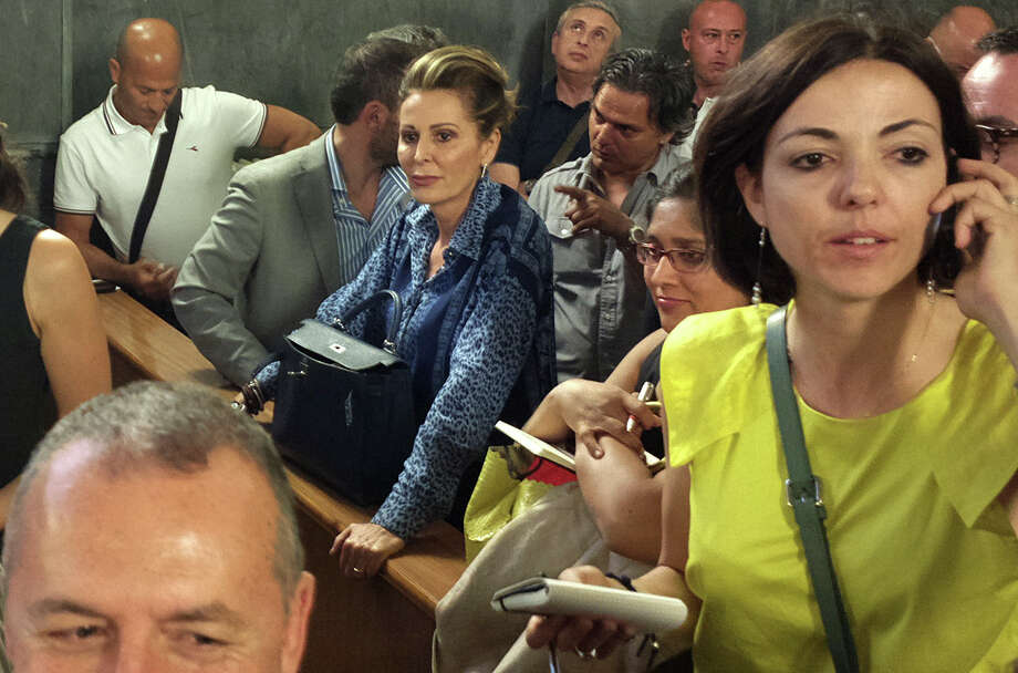 "Daniela Santanche', center, former undersecretary to the minister of Platform Accomplishment during Berlusconi cabinet, listens to the verdict against Silvio Berlusconi in a courtroom in Milan, Italy, Monday, June 24, 2013. A Milan court has convicted former Italian Premier Silvio Berlusconi of paying for sex with an under-age prostitute during infamous ""bunga bunga"" parties at his villa and then using his influence to try to cover it up. Berlusconi, 76, was sentenced to seven years in prison and barred from public office for life. The ban on holding office could mean the end of Berlusconi's two-decade political career. However, there are two more levels of appeal before the sentence would become final. Photo: AP"