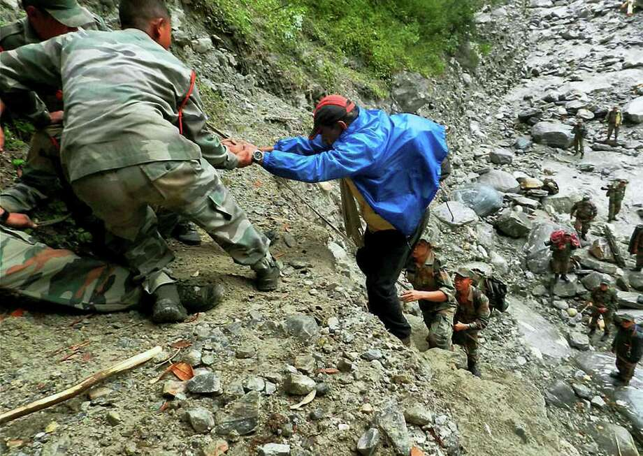 Indian army soldiers help a man up a slope at Pindari Glacier, in the northern Indian state of Uttarakhand, Thursday, June 27, 2013. Authorities in northern India on Thursday conducted mass cremations of hundreds of people who were killed by devastating floods and landslides that struck nearly two weeks ago. Photo: AP
