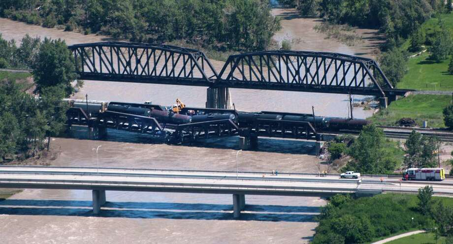 Crews work at the scene of a rail bridge collapse and railcars derailment over the Bow River, southeast of downtown Calgary, Canada on Thursday, June 27, 2013. Photo: AP