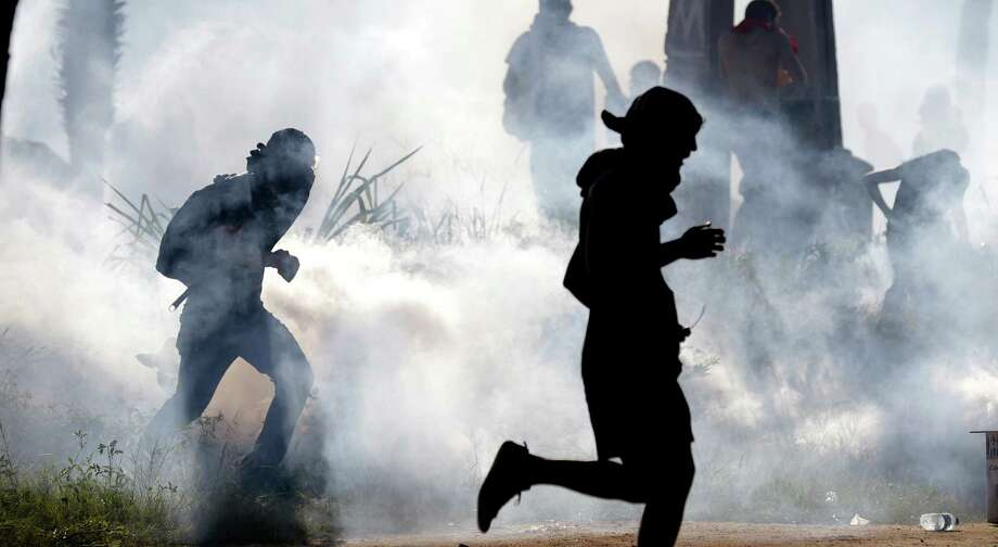 Protesters run from tear gas dispersed by police a few miles from the soccer stadium where Spain and Italy met in a Confederations Cup soccer semifinals' match in Fortaleza, Brazil, Thursday, June 27, 2013. About 5,000 anti-government protesters battled police on Thursday near the stadium. Demonstrators are angered about corruption and poor public services despite a heavy tax burden. Protests are also denouncing the billions of dollars spent to host the World Cup and the 2016 Olympics. Photo: AP