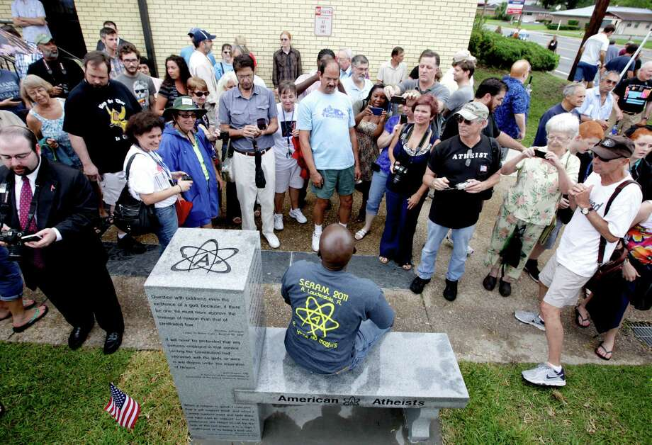 People gather around to sit and take photos during the unveiling of an Atheist monument outside the Bradford County Courthouse on Saturday, June 29, 2013 in Stark, Fla.  The New Jersey-based group American Atheists unveiled the 1,500-bound granite bench Saturday as a counter to the religious monument in what's called a free speech zone. Group leaders say they believe it's the first such atheist monument on government property. About 200 people attended the event. Photo: AP