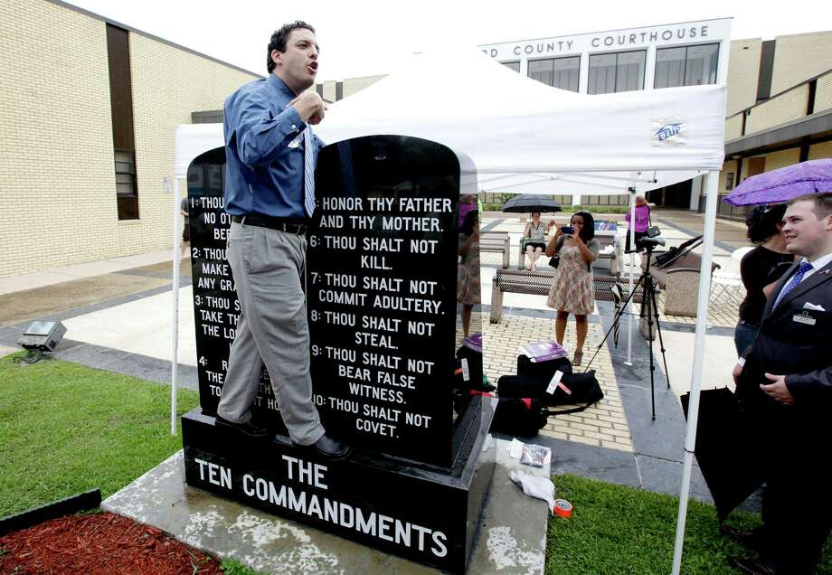 David Silverman, president of American Atheists, stands on a Ten Commandments and says why he thinks it shouldn't be there after Eric Hovind (not pictured), with Creation Today, stood on the new Atheist bench and preached his beliefs during the unveiling of an Atheist monument outside the Bradford County Courthouse on Saturday, June 29, 2013 in Stark, Fla. The New Jersey-based group American Atheists unveiled the 1,500-bound granite bench Saturday as a counter to the religious monument in what's called a free speech zone. Group leaders say they believe it's the first such atheist monument on government property. About 200 people attended the event. Photo: AP