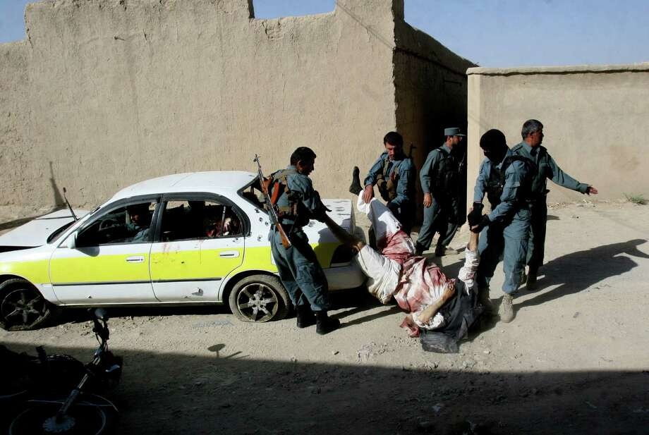 Afghan police men carry the lifeless body of a Taliban fighter in Ghazni province east of Kabul, Afghanistan, Thursday, June, 27, 2013. Authorities say Taliban fighters ambushed a national police patrol in western Afghanistan, killing a commander and several of his men. Photo: AP