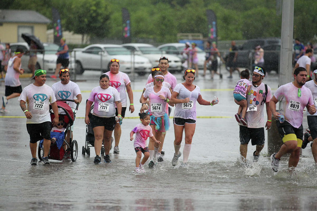 Con: Flooding happens. Frequently. Just like this group of Color Me Rad runners, San Antonio residents end up wading through the streets after storms.