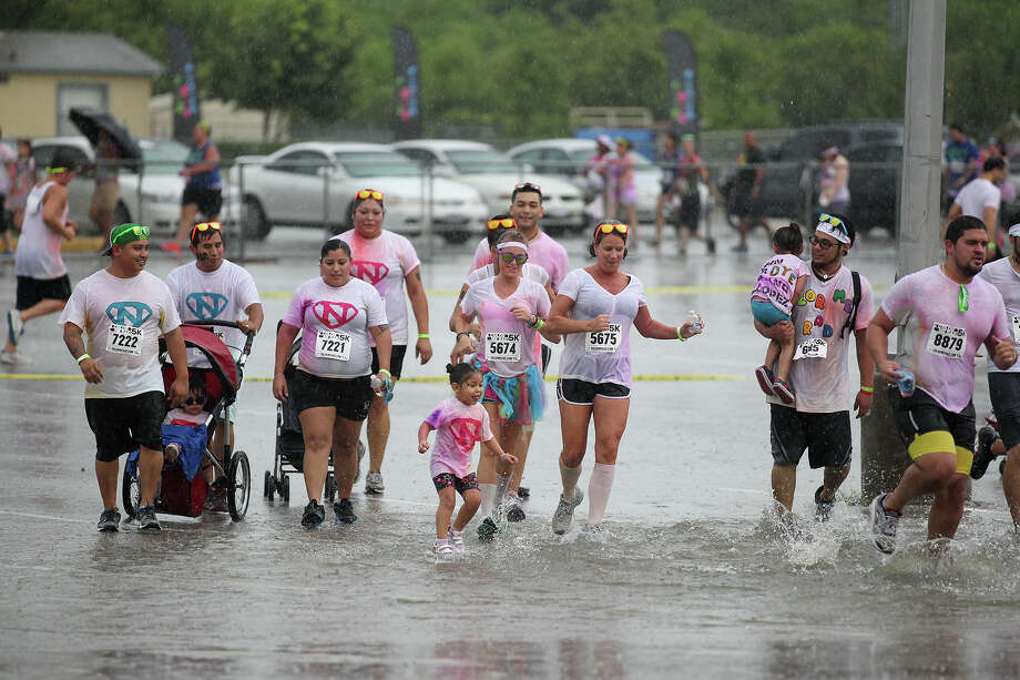 Con: Flooding happens. Frequently. Just like this group of Color Me Rad runners, San Antonio residents end up wading through the streets after storms.  Photo: JERRY LARA, San Antonio Express-News / © 2013 San Antonio Express-News
