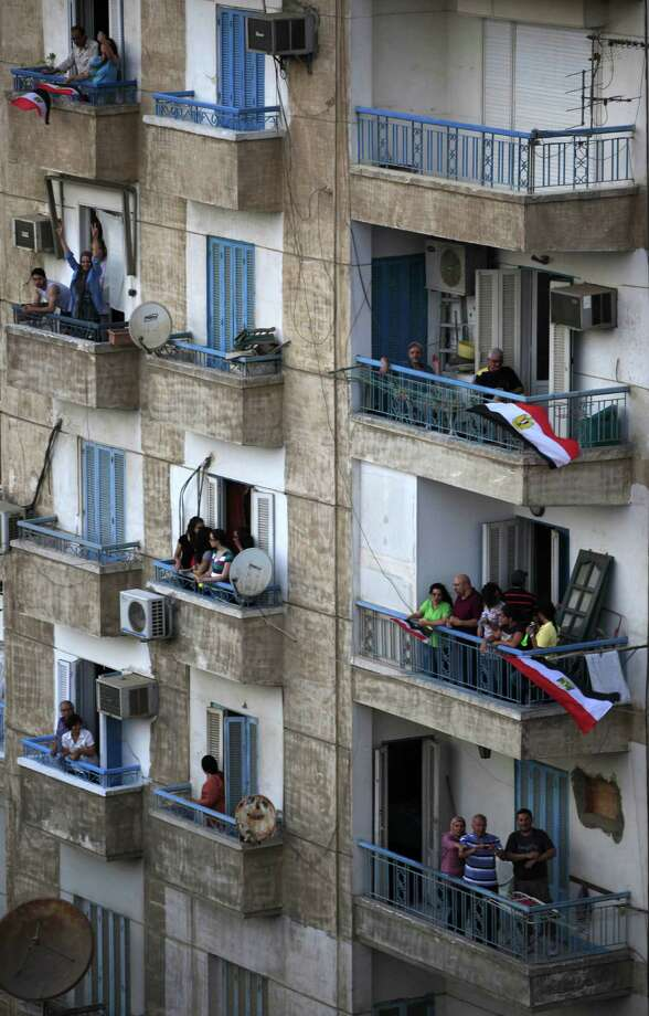 Egyptians wave the national flags from their balconies as they watch opponents of Egypt's Islamist President Mohammed Morsi protest outside the presidential palace in Cairo, Egypt, Sunday, June 30, 2013. Hundreds of thousands of opponents of Egypt's Islamist president poured out onto the streets in Cairo and across much of the nation Sunday, launching an all-out push to force Mohammed Morsi from office on the one-year anniversary of his inauguration. Fears of violence were high, with Morsi's Islamist supporters vowing to defend him. Photo: Khalil Hamra
