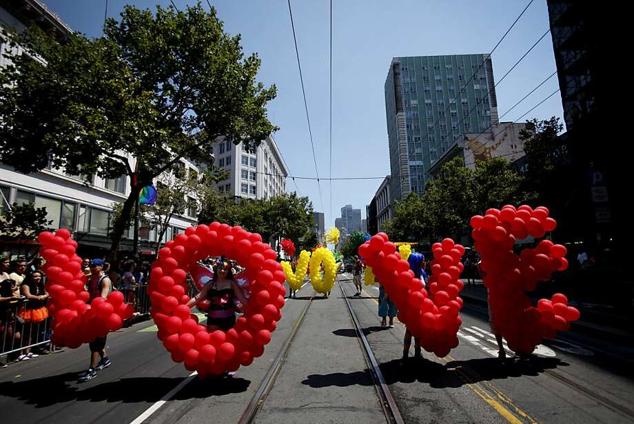 "SAN FRANCISCO - JUNE 30:  Participants caring balloons to form the message ""Love Won"" walk in the 43rd annual San Francisco Lesbian, Gay, Bisexual, Transgender (LGBT) Pride Celebration & Parade June 30, 2013, in San Francisco, California.  The annual S.F. Pride Parade occurred just days after same-sex marriages were reinstated in California following the recent Supreme Court rulings.  (Photo by Sarah Rice/Getty Images) Photo: Sarah Rice, Getty Images"