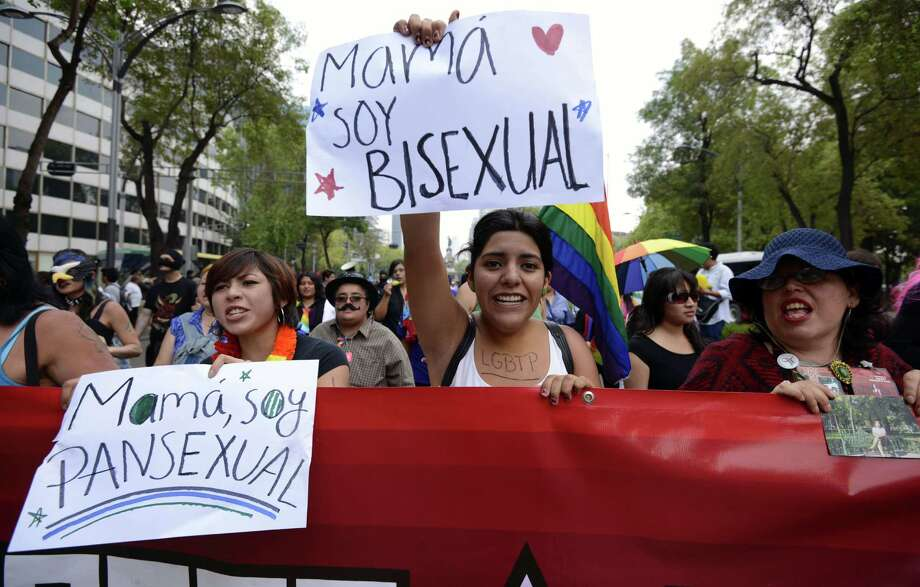 "People march during the 35th Gay Pride Parade along Reforma Avenue in Mexico City on June 29, 2013. The signs read, ""Mom, I´m pansexual"" and ""Mom, I´m bisexual"". AFP PHOTO/Alfredo EstrellaALFREDO ESTRELLA/AFP/Getty Images Photo: ALFREDO ESTRELLA, AFP/Getty Images / AFP"