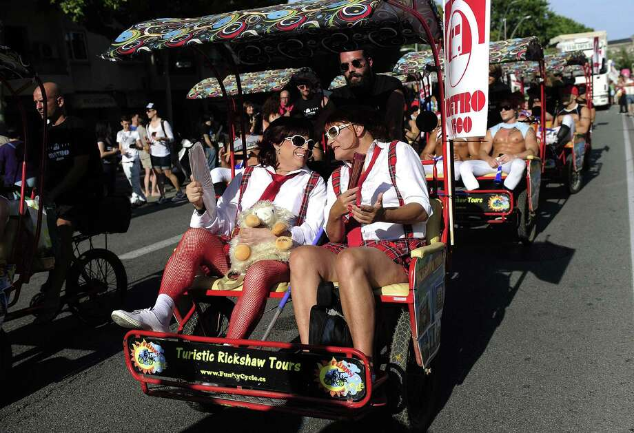 Participants sit in pedicabs during the Gay and Lesbian Pride parade in Barcelona on June 29, 2013. AFP PHOTO / JOSEP LAGOJOSEP LAGO/AFP/Getty Images Photo: JOSEP LAGO, AFP/Getty Images / AFP