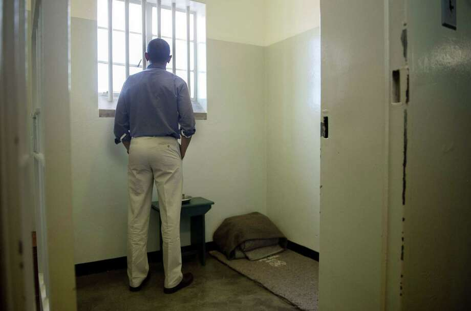 Paying homage to the former South African president, who is critically ill in the hospital, President Barack Obama stared into the stark cell, on Sunday, where Nelson Mandela, 94, spent two thirds of his 27 years in jail. Photo: JIM WATSON, Staff / AFP ImageForum