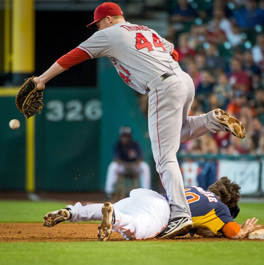 Astros shortstop Jake Elmore dives back to first as the ball gets away from Angels first baseman Mark Trumbo. Brandon Barnes scored for the Astros on the play.  Angels third baseman Alberto Callaspo was charged with an error.