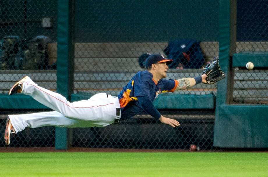 Astros center fielder Brandon Barnes dives for triple off the bat of Angels second baseman Howie Kendrick during the third inning.