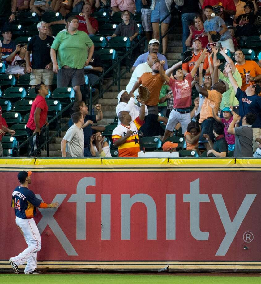 Astros right fielder J.D. Martinez watches as fans reach for a home run off the bat of Angels first baseman Mark Trumbo.