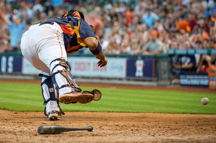 Astros catcher Carlos Corporan reaches for a throwing error by shortstop Jake Elmore allowing Angels outfielderJosh Hamilton to score during the eighth inning,