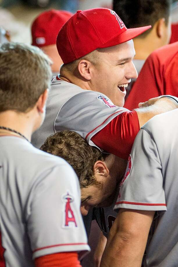 Angels outfielder Mike Trout, top, celebrates with Josh Hamilton after he scored on a throwing error by Astros shortstop Jake Elmore during the eighth inning.