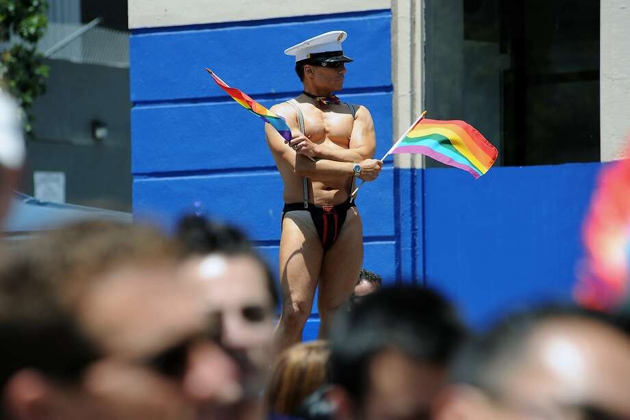 A man waves flags in the crowd as he watches the Annual Pride Parade in San Francisco on June 30th, 2013. Photo: Michael Short, Special To The Chronicle