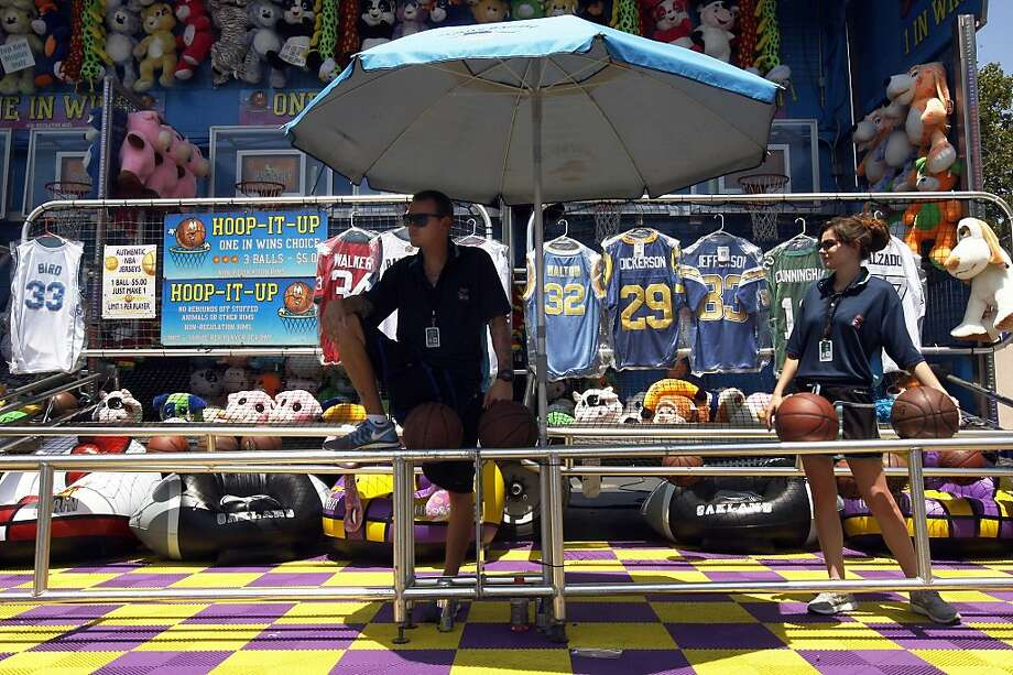 Joshua Clabaugh and Tera Weber wait for fairgoers to shoot hoops in the heat at the Alameda County Fair. Photo: Rohan Smith, The Chronicle