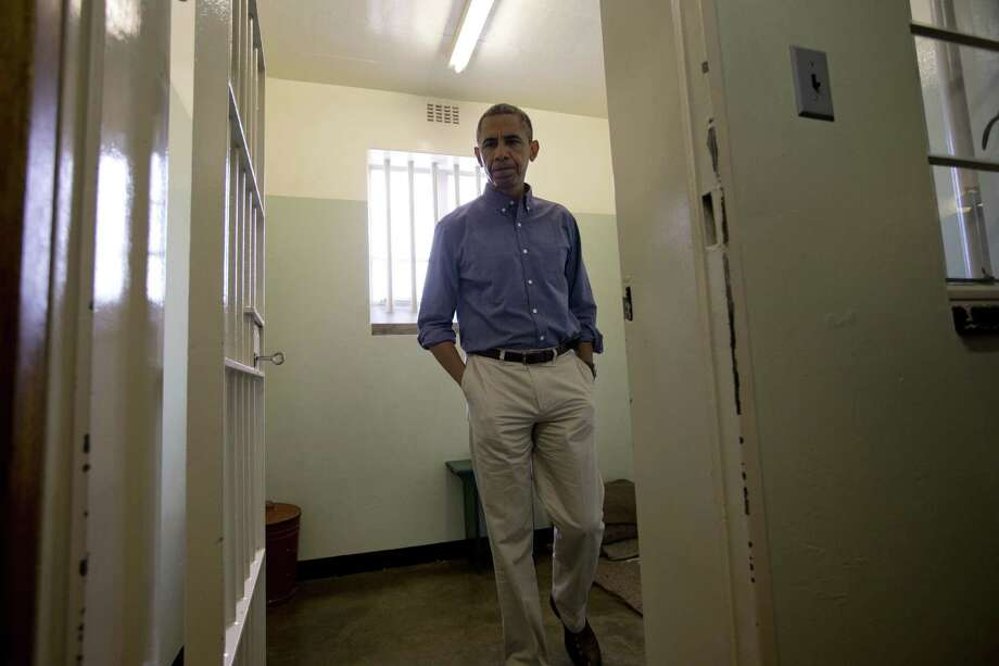 President Barack Obama walks from Section B, prison cell No. 5 on Robben Island, Nelson Mandela's cell for 18 years of his 27-year prison term on the island. Photo: Carolyn Kaster / Associated Press