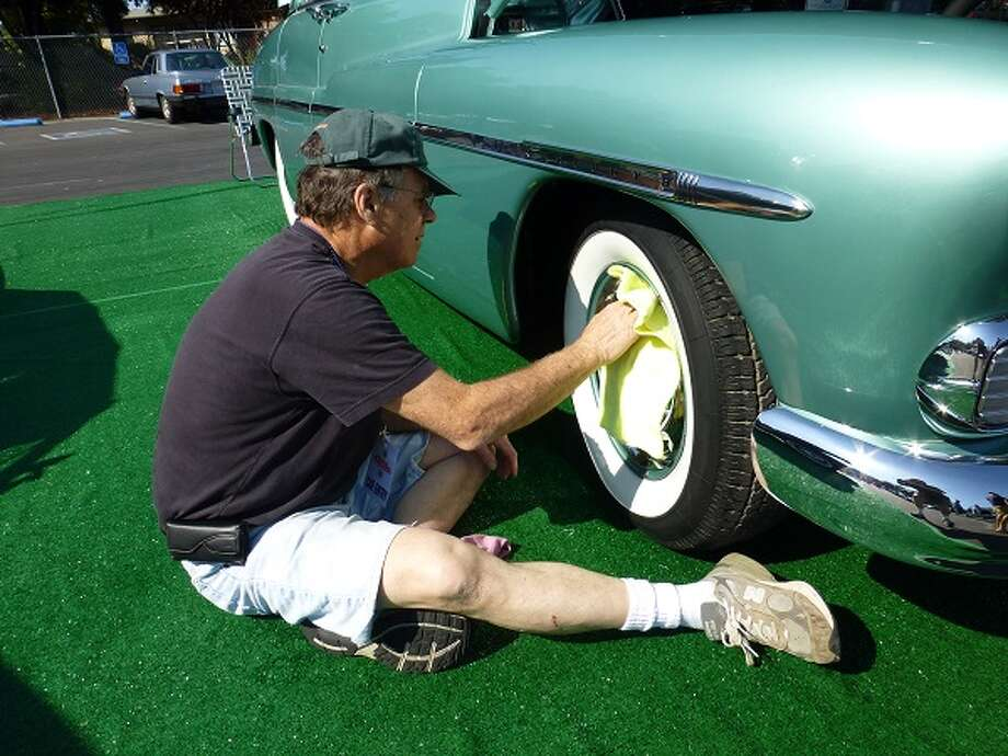 Vince O'Brien polishes the right front wheel of his 1950 Mercury.
