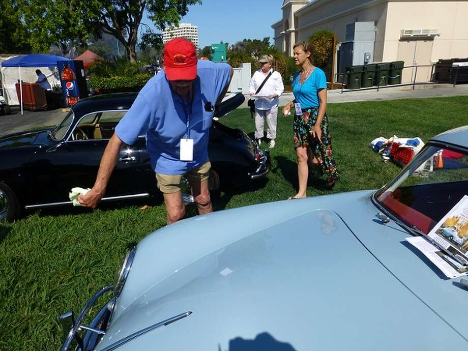William Disser dusts off the fender of his 1958 Porsche. The car has 216,000 miles on it and he's the original owner. He bought the car at British Motors in Baltimore, Md., and replaced the Porsche drum brakes with disks some time in the 1970s.