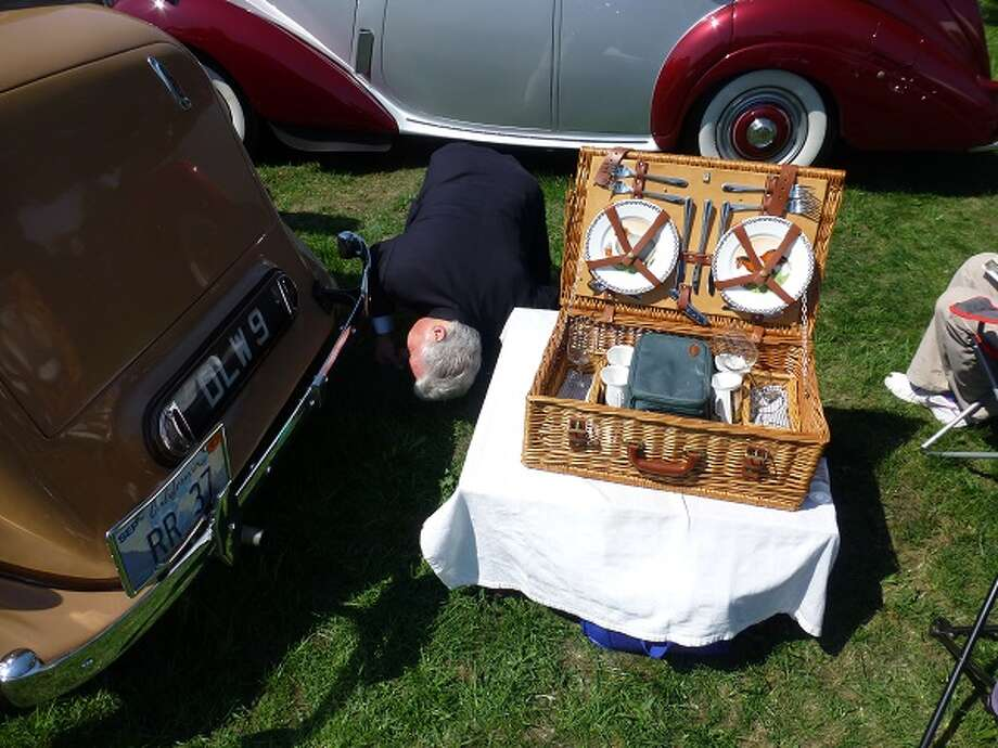 Concours judge Peter Grassi peers under David Clover's 1937 Rolls-Royce. The picnic basket is up to Rolls standards.