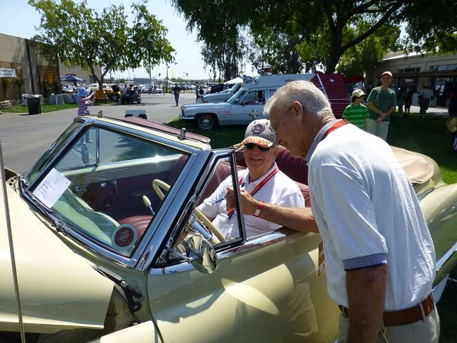 1949 Cadillac convertible. Owner Charles Thompson (left) chats with chief judge Ed Gunther.