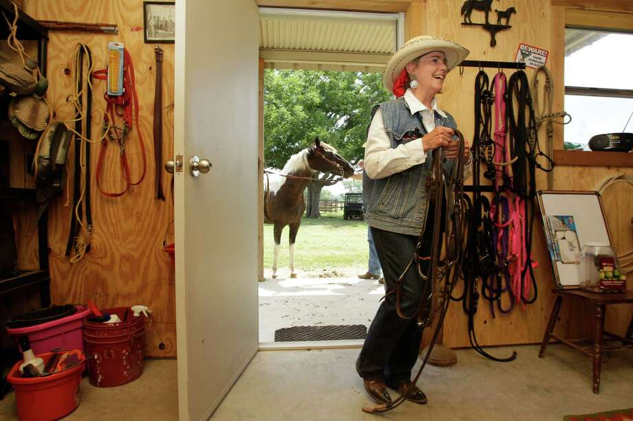 Mary Chandler puts up tack after riding her horse, Zella, on the Half Circle O Ranch Friday, June 28, 2013, in Sealy.  Her family has been on the land since 1885. Farmers and ranchers in Austin and Waller counties are fighting a private company's plans to pump 20 million gallons of water a day from the aquifer beneath them and send it to the growing Fort Bend County suburbs. Opponents are worried about the availability of water, as well as subsidence. She is worried about losing her water and subsidence if the the permits are granted. Photo: Melissa Phillip, Houston Chronicle / © 2013  Houston Chronicle
