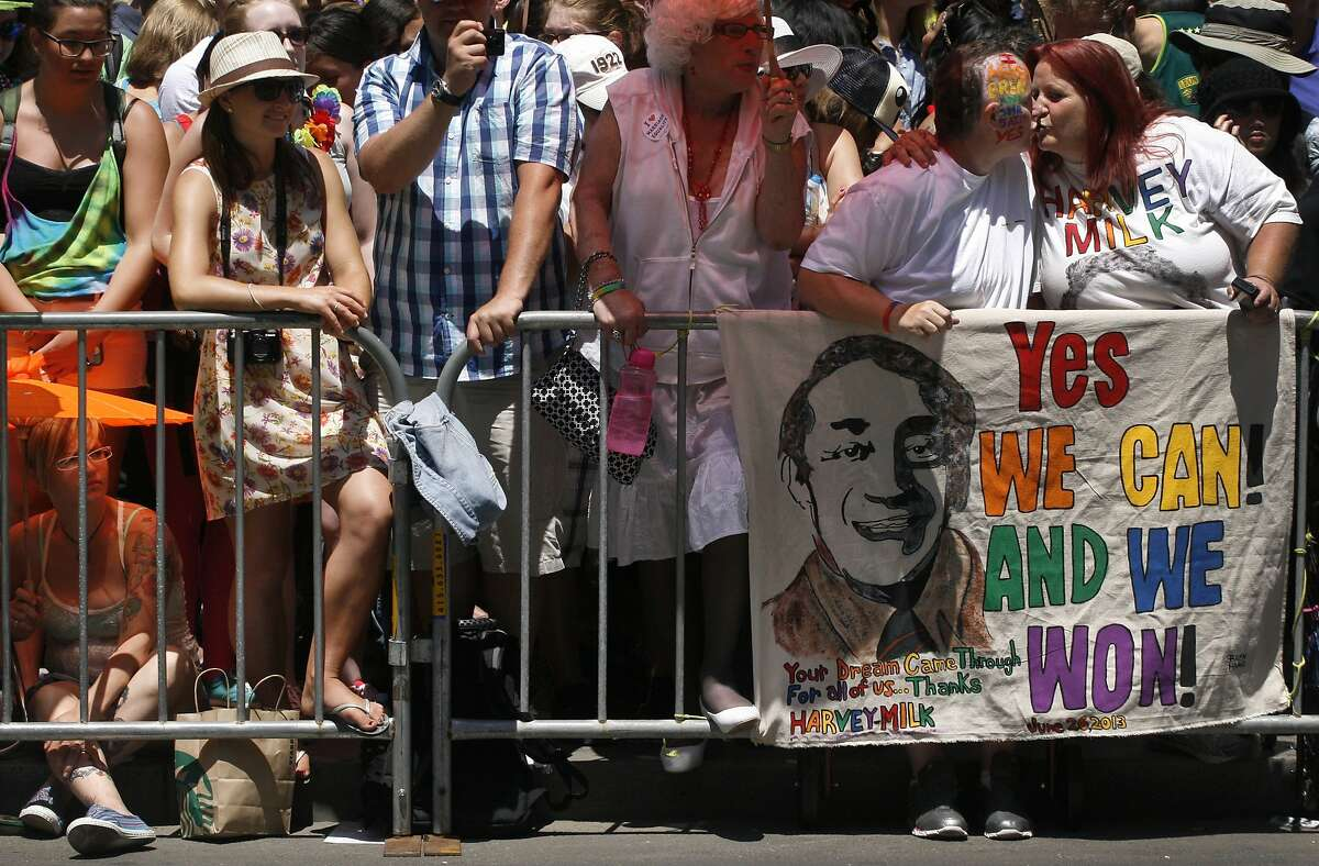 Lisa Siegrist and Bren Haag kiss behind their Harvey Milk sign as they watch the 2013 Pride Parade in San Francisco.