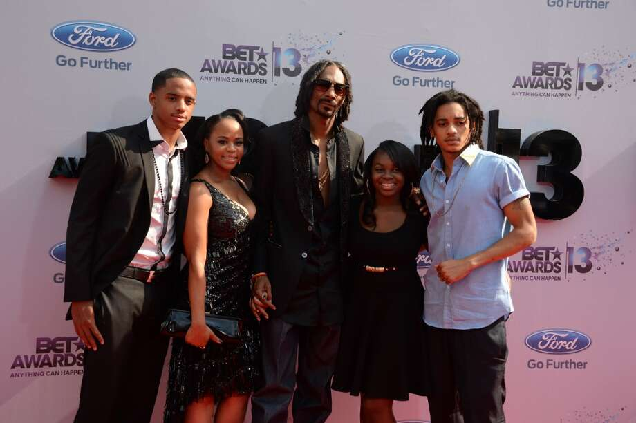 Snoop Lion (C), formerly Snoop Dog, arrives with his family  for the 2013 BET Awards at the Nokia Theatre L.A. Live in Los Angeles, California June 30, 2013.  The awards ceremony recognize Americans in music, movies, sports and other fields of entertainment over the past year.  AFP PHOTO / ROBYN BECK        (Photo credit should read ROBYN BECK/AFP/Getty Images)