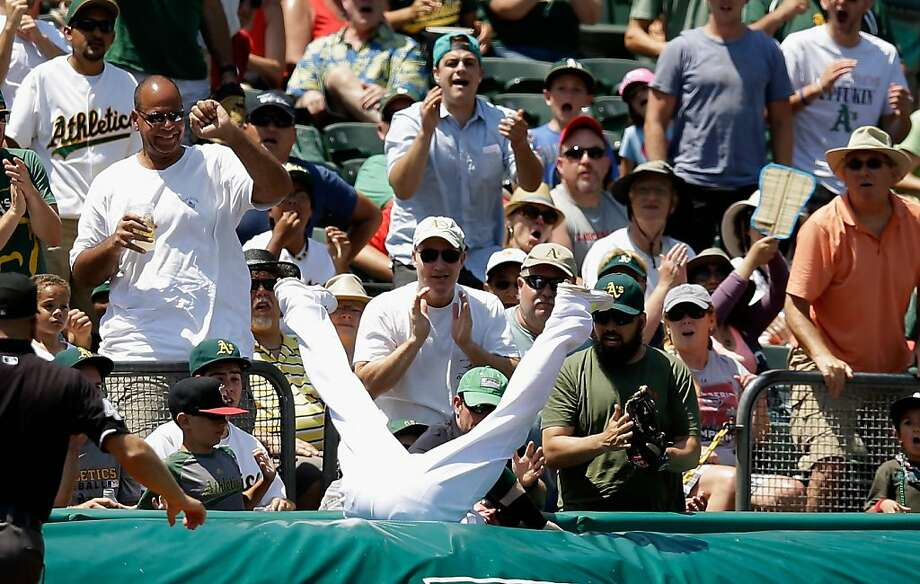Fans cheer as the A's Josh Donaldson caught Matt Carpenter's foul pop in the fourth inning, then had his legs undercut by the tarp, sending him tumbling. Photo: Ezra Shaw, Getty Images