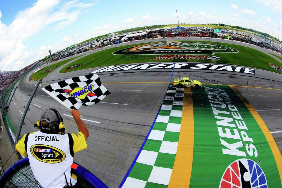 Matt Kenseth takes the checkered flag at the Quaker State 400 in Sparta, Ky., on Sunday, a day after rain postponed the Sprint Cup race. Jimmie Johnson had led most of the way. Photo: Sean Gardner / Getty Images