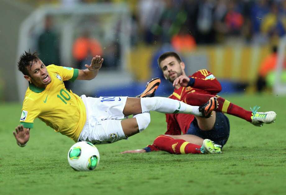 Gerard Pique, right, takes down Brazil's Neymar with a rugged tackle that earned the Spaniard a red card in the 68th minute. Photo: Andre Penner, STF / AP