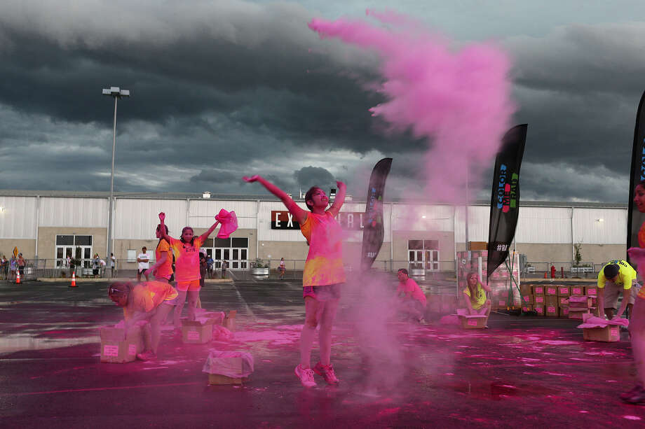 Abby Rodriguez, 17, throws a handful of colored cornstarch during the Color Me Rad 5K. At the finish line, runners emerge from a cornstarch fog, the culmination of participants throwing the cornstarch at and on each other as they complete the route. Photo: Photos By Jerry Lara / San Antonio Express-News