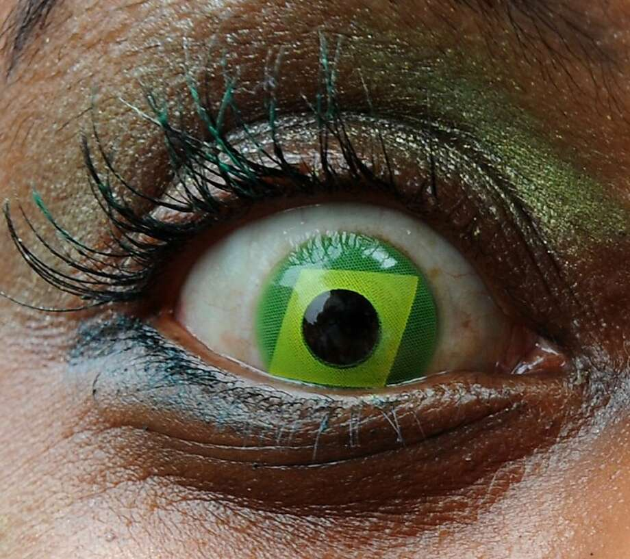 Don't it make my brown eyes green: A demonstrator wearing a contact lens resembling the Brazilian national flag marches in a street near the 