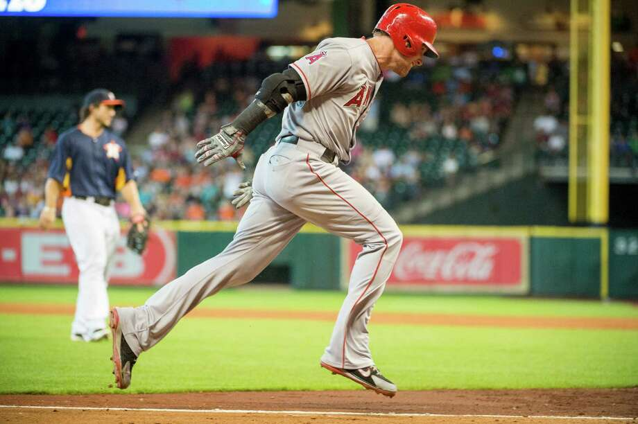 Josh Hamilton heads for home as a throwing error by Astros shortstop Jake Elmore in the eighth inning gives the Angels a crucial insurance run. Photo: Smiley N. Pool / © 2013  Smiley N. Pool