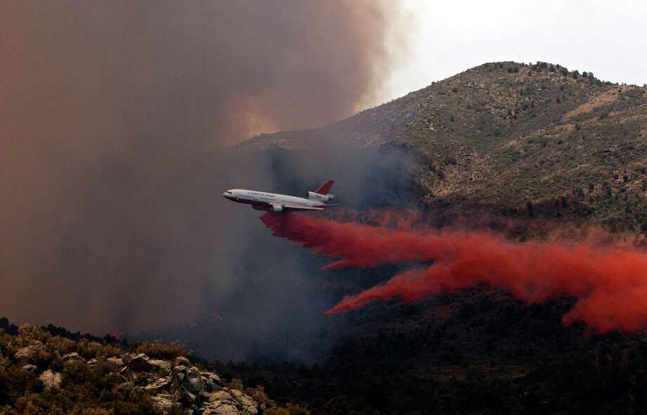 Tanker 910 makes a retardant drop on the Yarnell Hill Fire to help protect the Double Bar A Ranch near Peeples Valley, Ariz., Sunday, June 30, 2013. The fire started Friday and picked up momentum as the area experienced high temperatures, low humidity and windy conditions. It has forced the evacuation of residents in the Peeples Valley area and in the town of Yarnell. (AP Photo/The Arizona Republic, Tom Story) Photo: Tom Story, Associated Press / The Arizona Republic