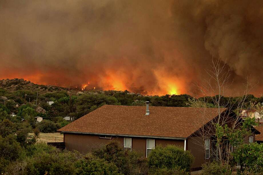 The Yarnell Hill Fire burns through the town of Yarnell, Ariz. on Sunday, June 30, 2013. The fire started Friday and picked up momentum as the area experienced high temperatures, low humidity and windy conditions. It has forced the evacuation of residents in the Peeples Valley area and in the town of Yarnell. (AP Photo/The Arizona Republic, Tom Story) Photo: Tom Story, Associated Press / The Arizona Republic